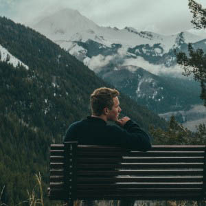 man on a bench in the mountains